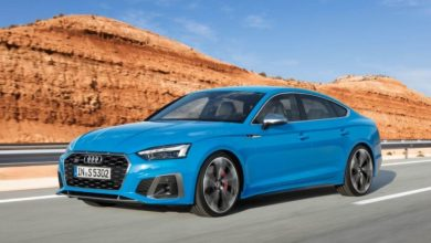 Audi S5 Sportback, blue color, running on the road with rocky mountains behind it