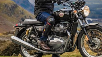 Man sitting on Royal Enfield bike wearing external knee guards