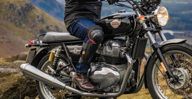 Man sitting on Royal Enfield bike wearing external knee guards