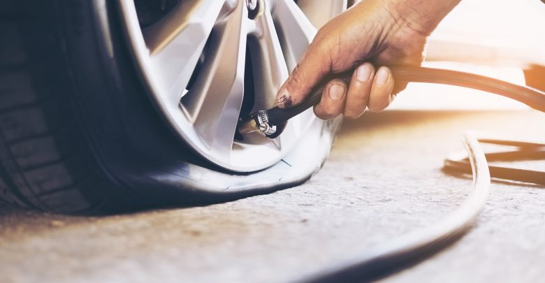 technician inflating flat tyre with a car tyre inflator